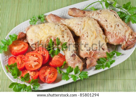 Fried chicken legs with cheese and tomato served on the white plate - stock photo