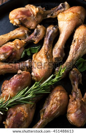 Fried chicken legs with spices, rosemary and mint on a wooden background