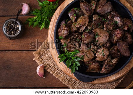 Fried chicken liver with onions and herbs. Top view