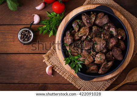 Fried chicken liver with onions and herbs. Top view - stock photo