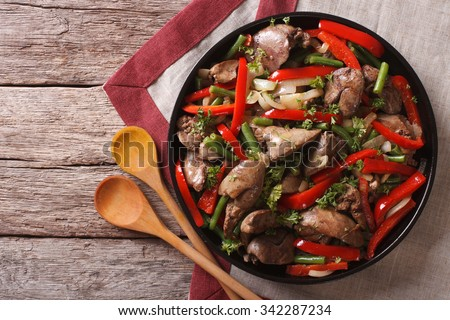 Fried chicken liver  with vegetables on a dish on the table. horizontal view from above