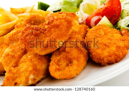 Fried chicken nuggets, French fries and vegetables - stock photo
