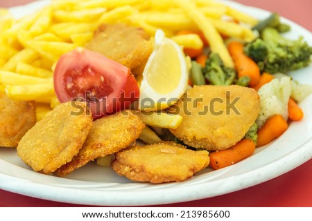 Fried chicken nuggets, French fries, lemon and vegetables - stock photo