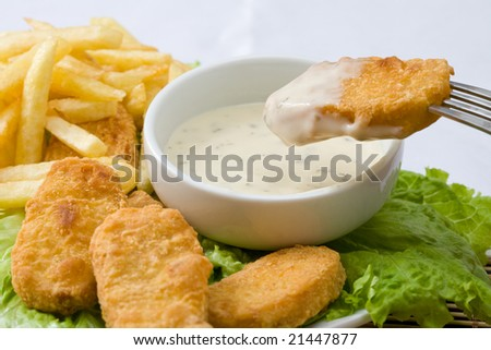 fried chicken nuggets with sauce for dipping and fries