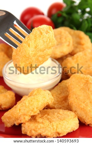 Fried chicken nuggets with vegetables and sauce isolated on white