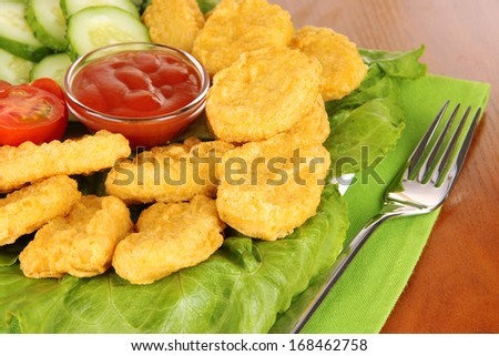 Fried chicken nuggets with vegetables and sauce on table  - stock photo