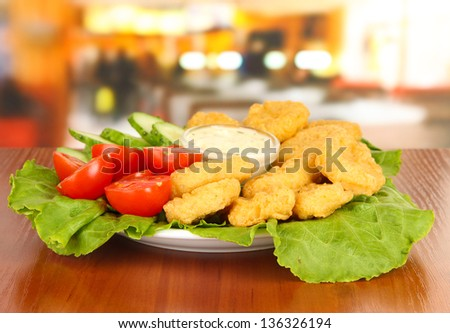 Fried chicken nuggets with vegetables and sauce on table in cafe - stock photo