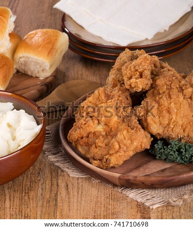 Fried chicken on a platter with mashed potatoes and rolls