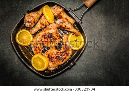 fried chicken on grill pan with sliced oranges - stock photo