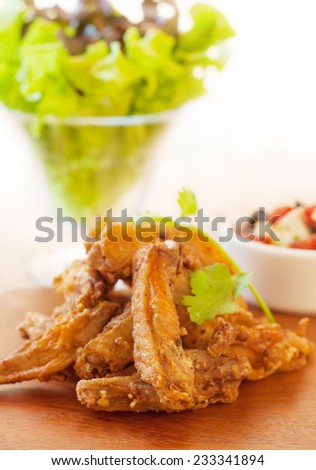 Fried chicken wing marinated with tabasco sauce served with greek salad. - stock photo