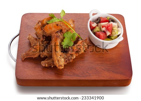 Fried chicken wing marinated with tabasco sauce served with greek salad, isolated on white. - stock photo