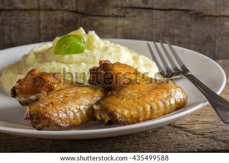 Fried chicken wings and mashed potatoes on plate with fork on wooden background - stock photo
