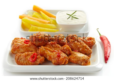 fried chicken wings and vegetables on white plate - stock photo