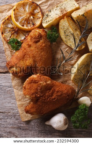 Fried chicken wings dipped in batter, with potato and lemon vertical view from above  - stock photo