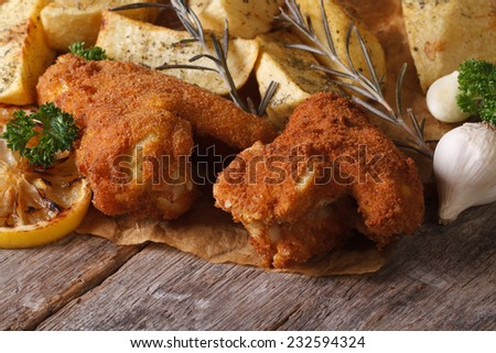 Fried chicken wings dipped in batter with potatoes close up on the table. horizontal   - stock photo
