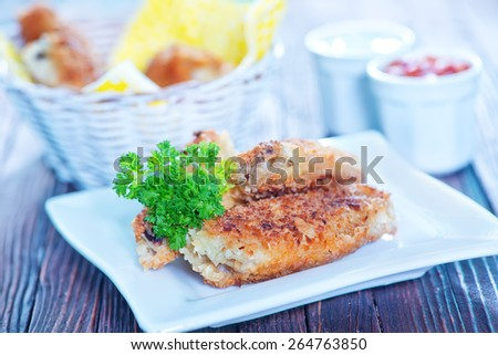 fried chicken wings in the basket and on a table - stock photo