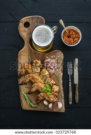 Fried chicken wings on rustic serving board, spicy tomato sauce, herbs and mug of light beer over black wooden backdrop, top view - stock photo