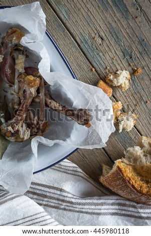 fried chicken wings on white plate on old wooden board with bread