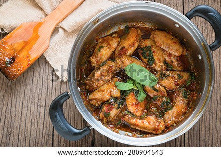 fried chicken with basil leaves in pot on old wood background