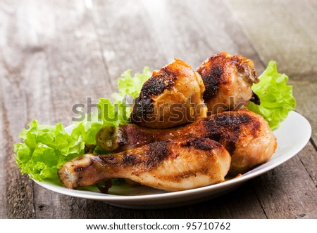 fried chicken with greens on wooden table - stock photo