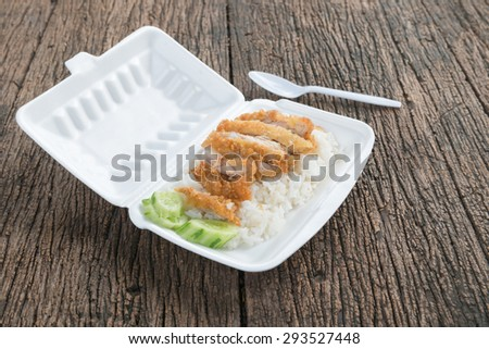 fried chicken with rice in foam box on wood background - stock photo