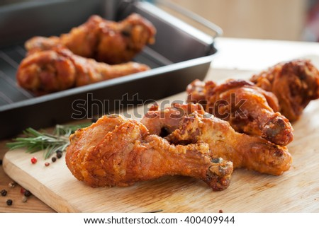 fried chicken with rosemary and pepper on chopping block - stock photo