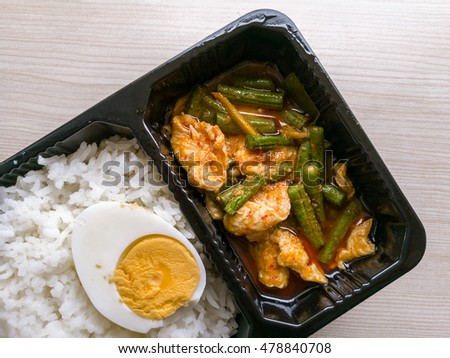 Fried chilly paste with chickens and boiled egg in black box Thai food ready to eat, top view