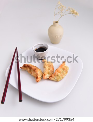 Fried Chinese pot stickers on white plate with soy dipping sauce, wood chopstick & vase with baby's breath flowers in the background - stock photo