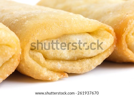 Fried chinese spring rolls on white surface.