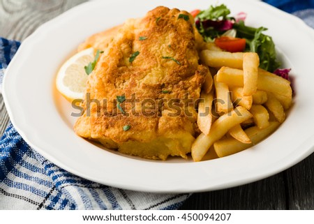 Fried cod with french fries on white plate.