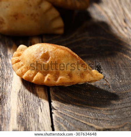 Fried colombian empanada on wooden table. Savory stuffed patty also known as pastel,pate or pirozhki - stock photo