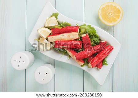 Fried crab sticks (surimi) and rocket salad with lemon slices - stock photo
