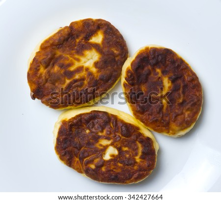 Fried curd pancakes on a gray background.