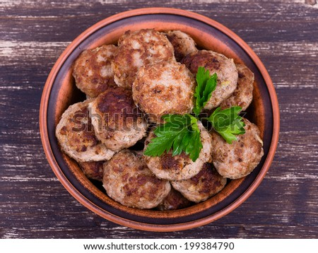 Fried cutlet in the plate on wooden table - stock photo