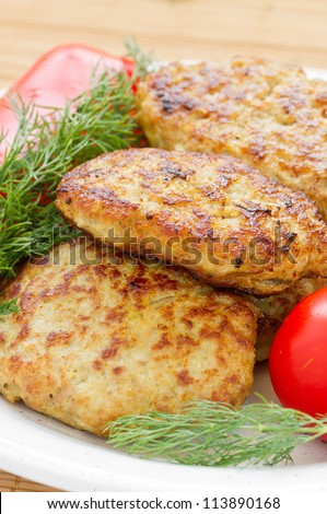 Fried cutlet with dill and tomatoes on a plate