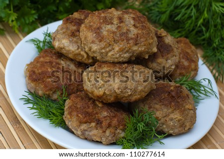 Fried cutlet with dill on a plate - stock photo