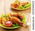 Fried drumsticks with french fries on the table - stock photo