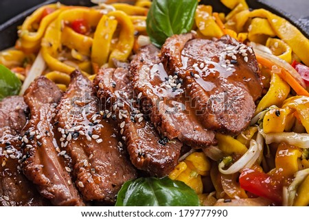 Fried duck meat with egg noodles closeup