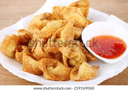 Fried dumpling and sauce on wood table
