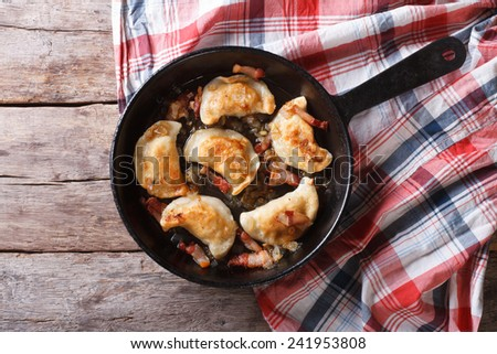 fried dumplings with onion and bacon in a frying pan. horizontal view from above  - stock photo