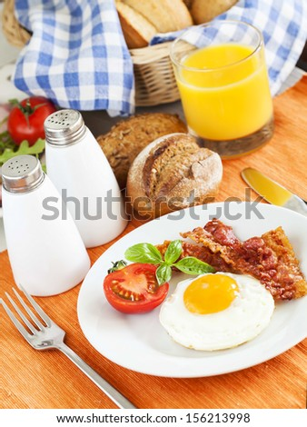 Fried egg and bacon for breakfast - stock photo
