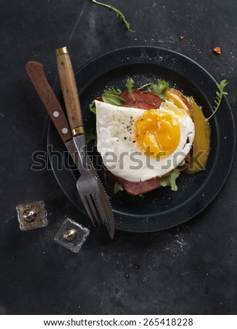 Fried egg and bacon on wholemeal bread, selective focus - stock photo