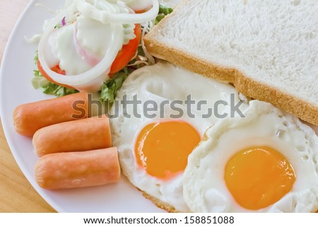 fried egg and fried sausage in a dish, american breakfast - stock photo