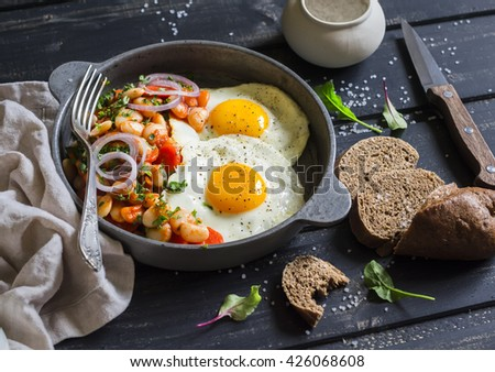 Fried egg, beans in tomato sauce with onions and carrots, fresh cucumbers and tomatoes, homemade rye bread - delicious  breakfast or snack  on dark wooden background - stock photo