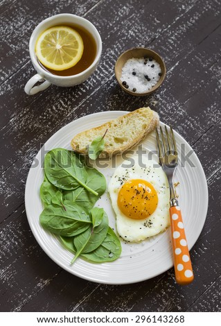 fried egg, fresh spinach and lemon tea - a healthy Breakfast, on a dark wooden surface - stock photo