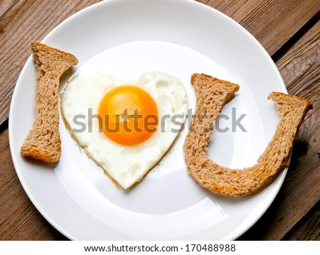 Fried egg heart and bread signs I love you - stock photo