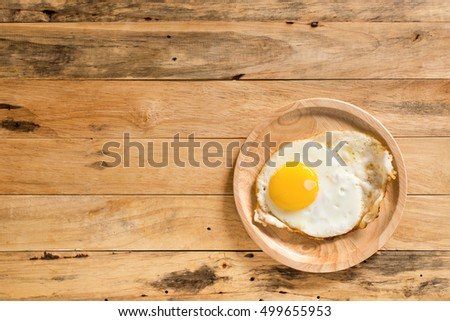fried egg i plate on wooden table.