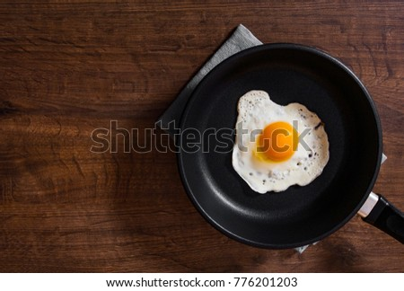 Fried egg in a frying pan on the brown wooden table background. with copy space. top view.