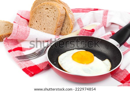 Fried egg in a frying pan, over white background - stock photo