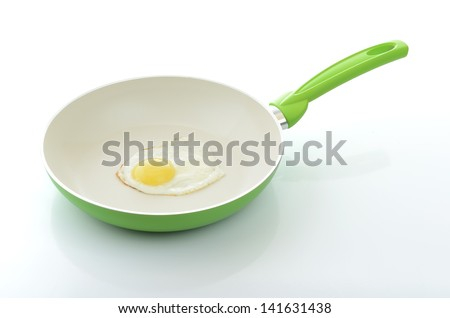 Fried egg in a green frying pan with ceramic coating. File contains a path to isolation. - stock photo
